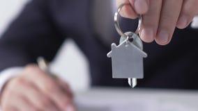 Encargado de las propiedades inmobiliarias que da la llave de la casa ideal al comprador, acuerdo de firma del alquiler almacen de metraje de vídeo
