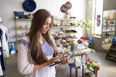 Encargado de sexo femenino del boutique que usa la tableta en tienda foto de archivo libre de regalías