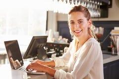 Encargado de sexo femenino del restaurante que trabaja en el contador Imagenes de archivo
