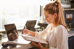 Encargado de sexo femenino del restaurante que trabaja en el contador Foto de archivo libre de regalías