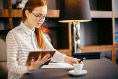 Encargado de sexo femenino joven sonriente del pelirrojo que usa la tableta digital moderna en la oficina Imagen de archivo libre de regalías