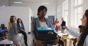 Encargado de sexo femenino negro joven triste encendido de la compañía multiétnica de la oficina, negándose a afrontar colegas tr almacen de video