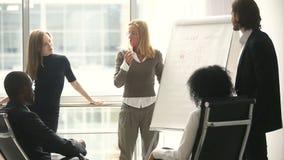 Encargado de sexo femenino que presenta nuevo plan del proyecto a los compañeros de trabajo en la reunión almacen de video