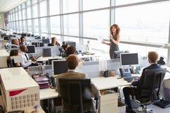 Encargado de sexo femenino que se dirige a trabajadores en oficina abierta del plan fotografía de archivo libre de regalías