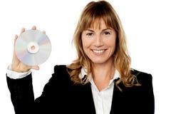 Encargado de sexo femenino sonriente que muestra el disco compacto fotografía de archivo libre de regalías