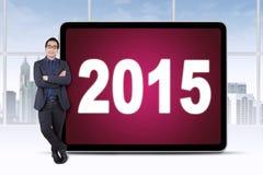 Encargado de sexo masculino con los números 2015 en un tablero Imagen de archivo