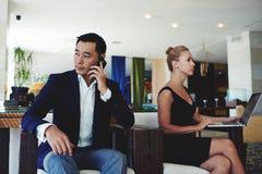 Encargado de sexo masculino confiado joven que llama con smartphone mientras que se sienta en oficina con el colega femenino Foto de archivo libre de regalías