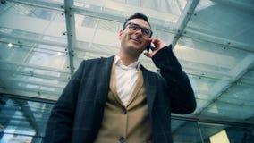 Encargado de sexo masculino corporativo feliz que habla en un teléfono móvil, cierre para arriba