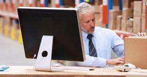Encargado de sexo masculino del almacén que trabaja sobre el ordenador almacen de video
