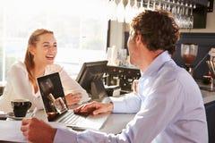 Encargado de sexo masculino del restaurante con el ordenador portátil que habla con la camarera Imágenes de archivo libres de regalías