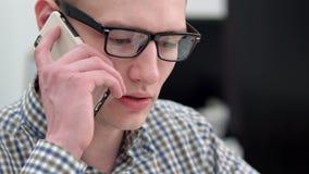 Encargado de sexo masculino joven que tiene conversación telefónica en la oficina metrajes