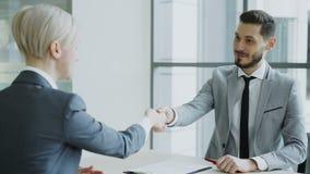 Encargado de sexo masculino de la hora que sacude la mano al candidato femenino después que tiene entrevista de trabajo en oficin