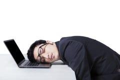 Encargado de sexo masculino que duerme en el ordenador portátil Imágenes de archivo libres de regalías