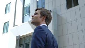 Encargado de sexo masculino que mira el rascacielos de la oficina, carrera urbana del negocio, empleo metrajes