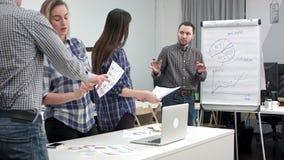 Encargado de sexo masculino que presenta el gráfico de sectores en flipboard a sus colegas almacen de metraje de vídeo