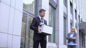 Encargado de sexo masculino triste con la caja de la materia que mira al jefe femenino que presume, despido de la compañía almacen de metraje de vídeo