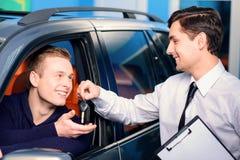Encargado de ventas que da llave del nuevo coche Imágenes de archivo libres de regalías