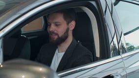 Encargado de ventas que entrega las llaves para servir que sentándose en el coche almacen de video
