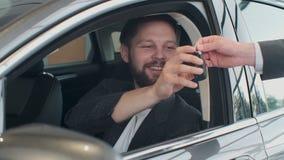Encargado de ventas que entrega las llaves para servir que sentándose en el coche almacen de metraje de vídeo