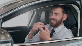 Encargado de ventas que entrega las llaves para servir que sentándose en el coche metrajes