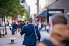 Encargado del inconformista con el teléfono elegante que camina en la calle foto de archivo