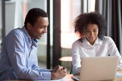 Encargado del mentor de la raza mixta que consulta al empleado africano de la enseñanza del cliente con el ordenador portátil fotografía de archivo libre de regalías