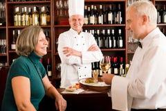 Encargado del restaurante con el personal en la barra de vino Imagen de archivo libre de regalías