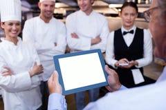 Encargado del restaurante que informa a su personal de la cocina Imágenes de archivo libres de regalías