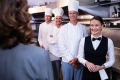 Encargado del restaurante que informa a su personal de la cocina Imagenes de archivo