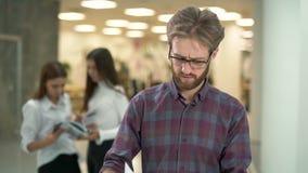 Encargado descontentado que revisa los documentos que se colocan en el pasillo de un centro de negocios Retrato de un barbudo des almacen de video
