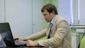 Encargado en su oficina que trabaja en el ordenador portátil Información de la lectura de una pantalla del ordenador portátil Ofi almacen de video