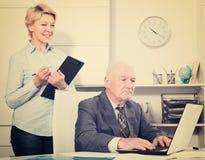 Encargado envejecido que trabaja con la secretaria imagenes de archivo