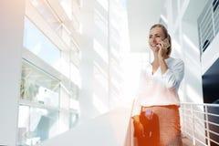 Encargado feliz joven de la mujer que habla en el teléfono elegante con su jefe sobre la reunión acertada con los clientes, Imagen de archivo