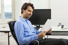 Encargado hermoso joven que se sienta en su escritorio en la oficina imagen de archivo