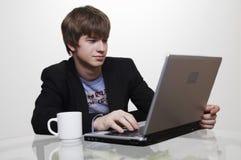 Encargado joven confidente con la computadora portátil Imagen de archivo libre de regalías