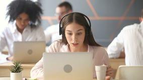 Encargado joven de la atención al cliente en auriculares que consulta al cliente, centro de atención telefónica