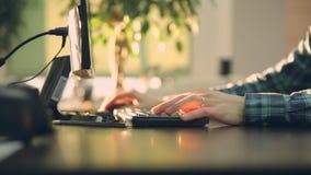 Encargado joven en la oficina que trabaja en el ordenador oficina de la puesta del sol almacen de video