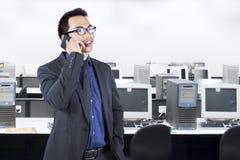 Encargado joven que habla en el teléfono en oficina Fotografía de archivo