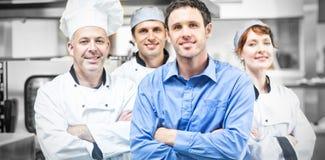 Encargado joven que presenta con algunos cocineros foto de archivo