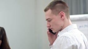 Encargado joven que tiene llamada de teléfono en la oficina metrajes