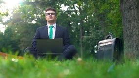 Encargado joven que trabaja en el ordenador portátil en el bosque, disfrutando de la naturaleza, escape de la oficina imagenes de archivo