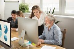 Encargado joven sonriente que ayuda al trabajador mayor con la oficina del ordenador fotos de archivo libres de regalías