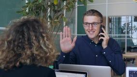 Encargado joven Talking en el alto cinco del teléfono móvil y del donante a su mujer del colega después de negocio acertado adent metrajes