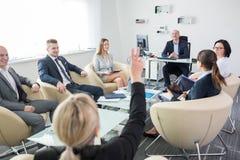 Encargado Looking At Executive que aumenta la mano durante la reunión Imagenes de archivo