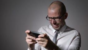 Encargado muy expresivo y emocional en la camisa blanca y lazo que juega a juegos en su smartphone metrajes