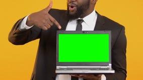 Encargado negro sonriente que señala el finger en el ordenador portátil con la pantalla verde, oferta de trabajo almacen de metraje de vídeo