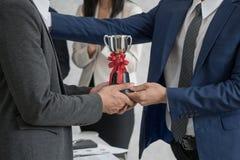 Encargado que da a empleado el premio del trofeo para el éxito en negocio fotografía de archivo