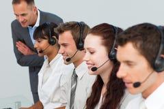 Encargado que habla con sus personas en un centro de atención telefónica Foto de archivo libre de regalías