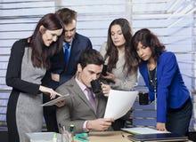 Encargado que se sienta en el escritorio, rodeado por su equipo del negocio Foto de archivo