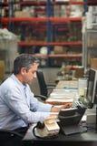 Encargado que trabaja en el escritorio en Warehouse Fotos de archivo libres de regalías